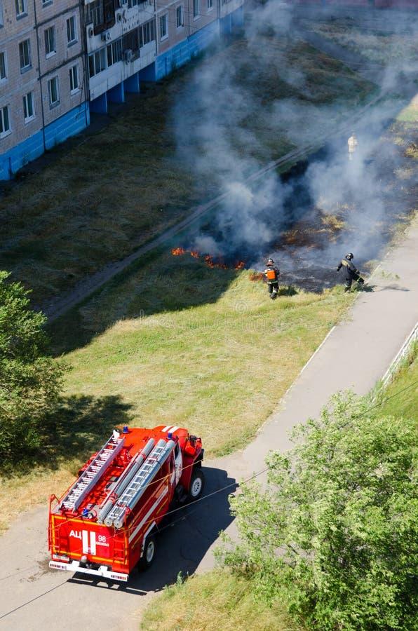 Brandvrachtwagen en brandweerlieden die uit een brandend gazon met gras in de stad zetten mening van hierboven en verticaal stock fotografie