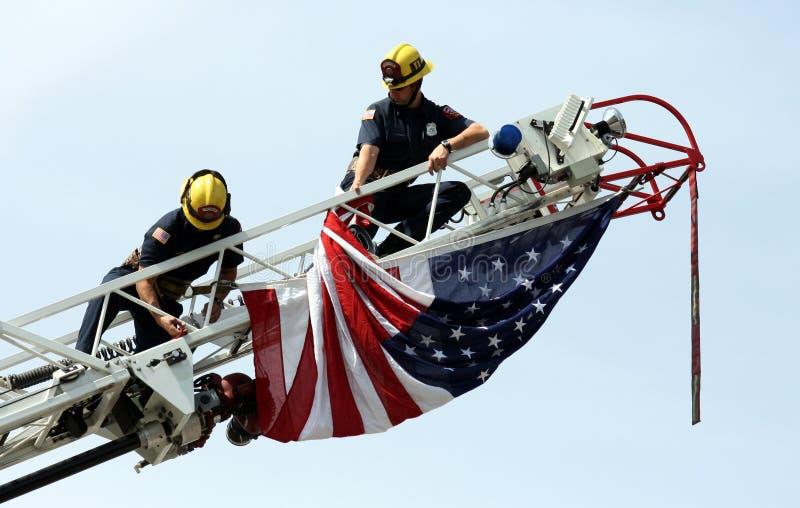 Brandweerlieden die de vlag van de V.S. hangen stock afbeeldingen