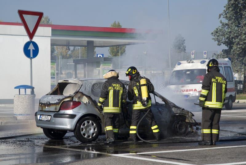 Brandweerlieden die een autobrand doven stock afbeelding