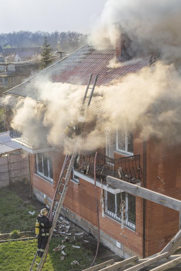 Brandweerlieden die een vuurzee met reusachtige vlammen van het branden bestrijden timbe royalty-vrije stock fotografie