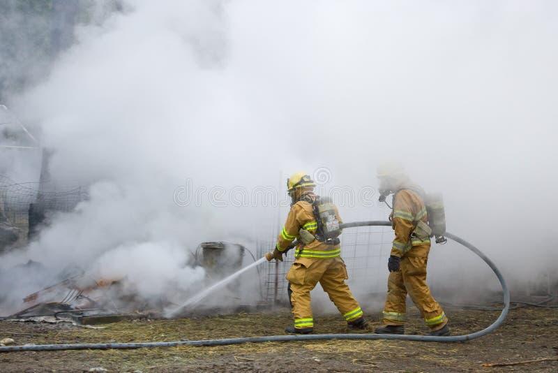 Brandweerlieden op de slang royalty-vrije stock fotografie