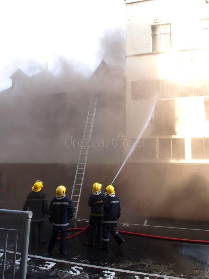 Brandweerlieden op het werk stock fotografie