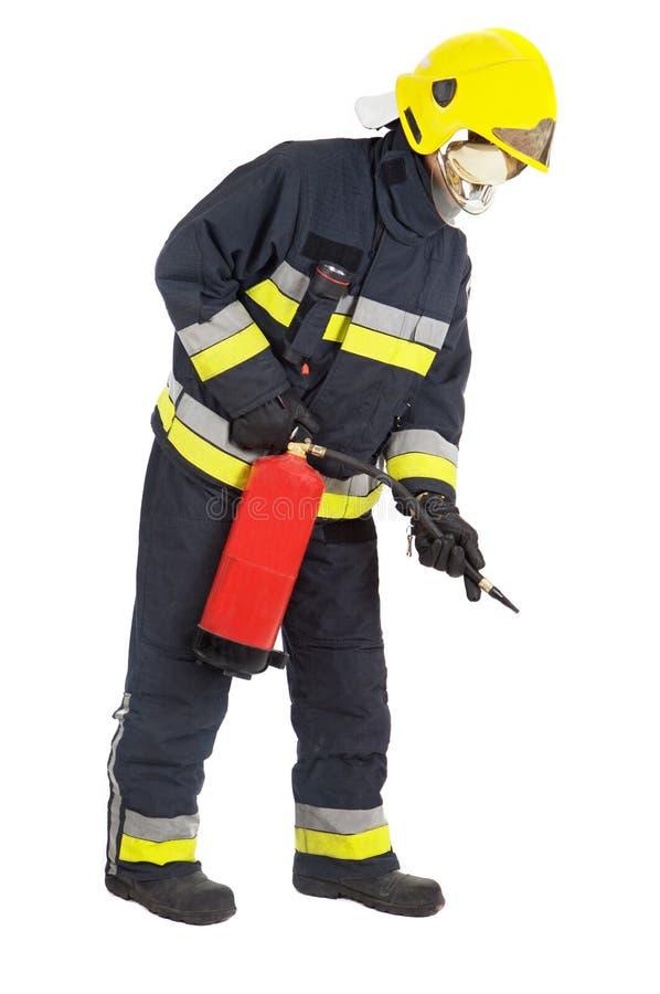 Brandweerman die de brand dooft stock fotografie