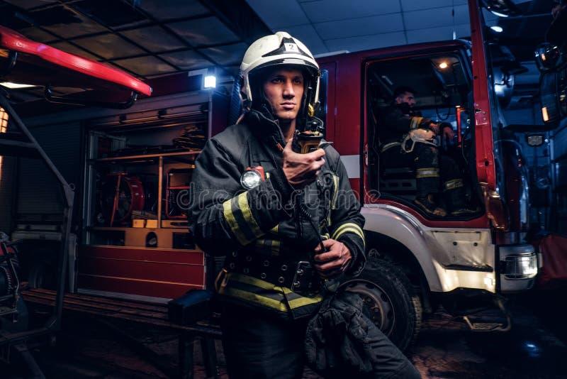 Brandweerman in een beschermende eenvormige status naast een brandvrachtwagen en het spreken op de radio De brandbrigade kwam bij stock fotografie