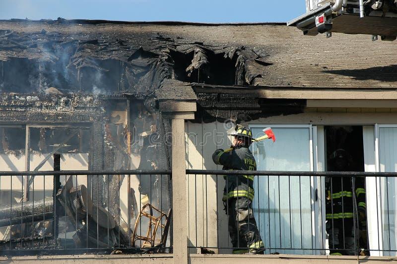 Brandweerman met bijl bij flatbrand royalty-vrije stock foto