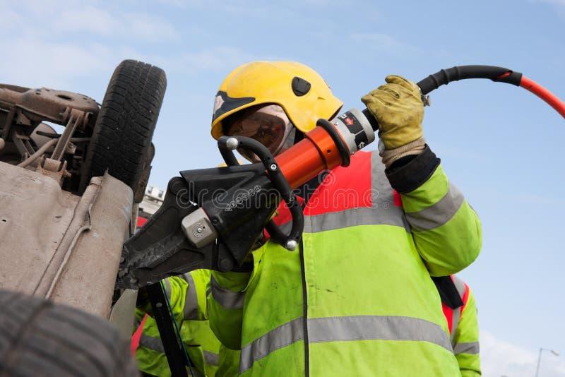 Brandweerman met de Wig van de Macht bij autoneerstorting, detail stock fotografie