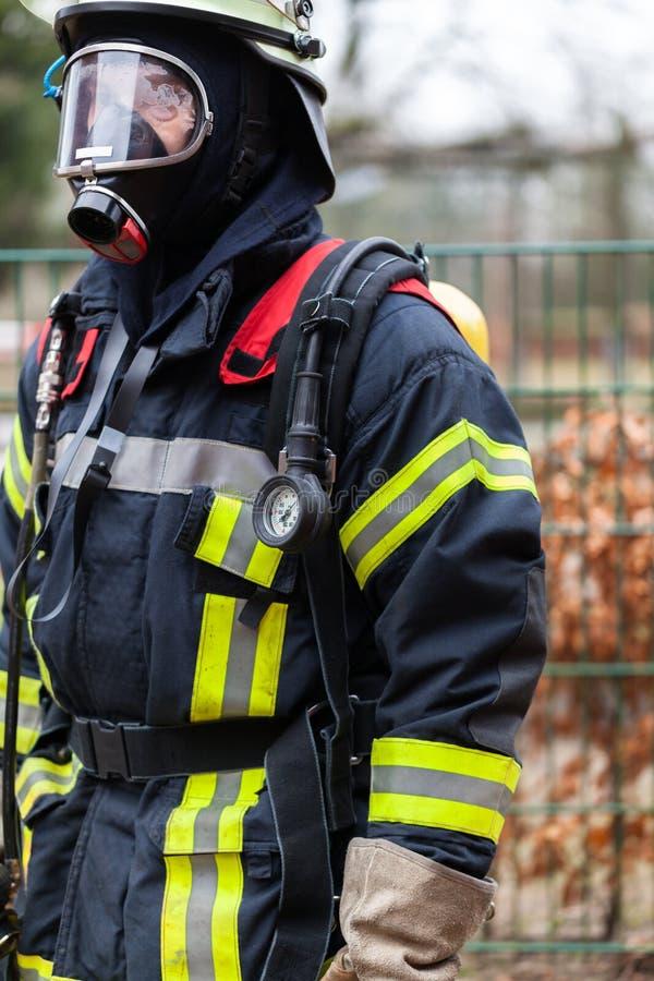 Brandweerman met vuurvast kleding en ademhalingsapparaat stock afbeelding