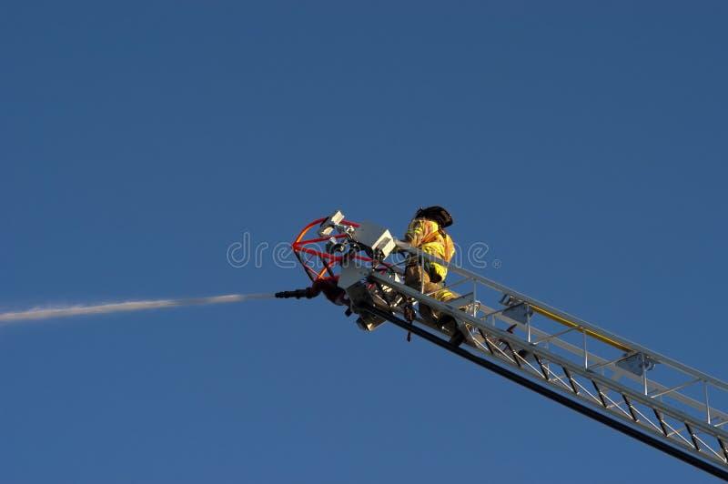 Brandweerman op het Water van de Nevel van de Vrachtwagen van de Ladder op Brand stock foto's
