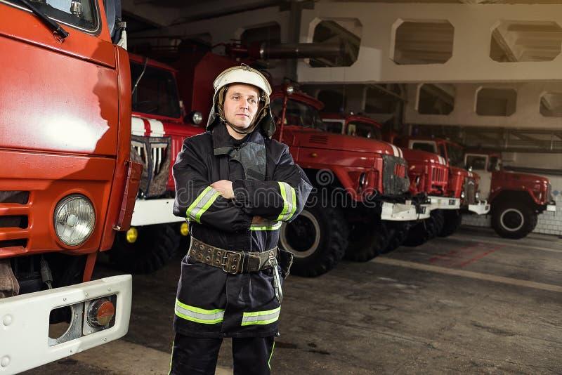 Brandweermanbrandbestrijder in actie die zich dichtbij een firetruck bevinden Emer royalty-vrije stock afbeelding