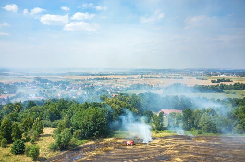 Brandweermanvrachtwagen die aan het gebied op brand werken stock foto's