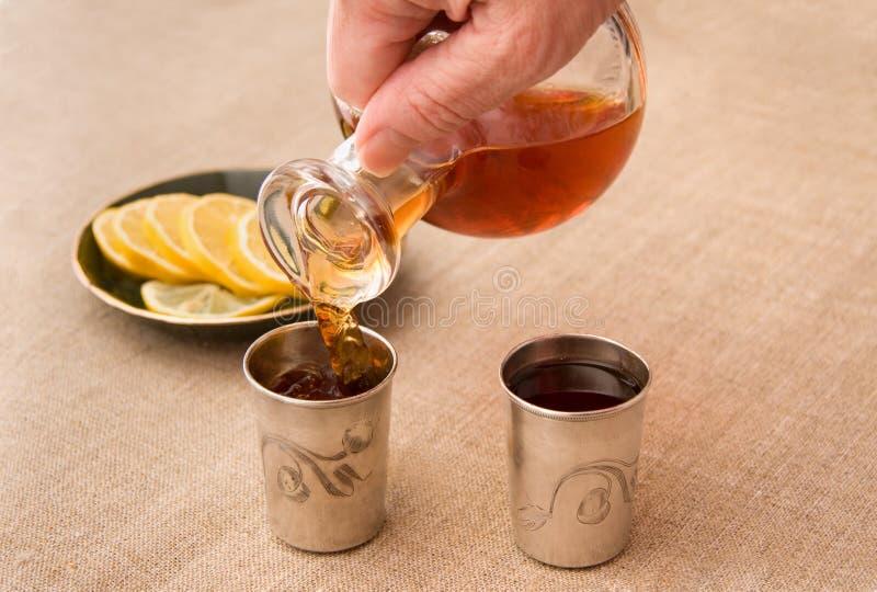 Brandy de colada en los recipientes de consumición de plata imagen de archivo
