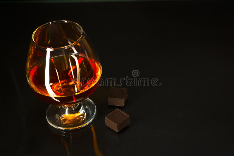 Brandy glass and chocolate on black background royalty free stock image