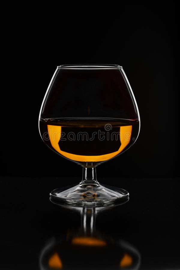 Brandy glass filled with half alcoholic drink on a black background in a beautiful light stock photography