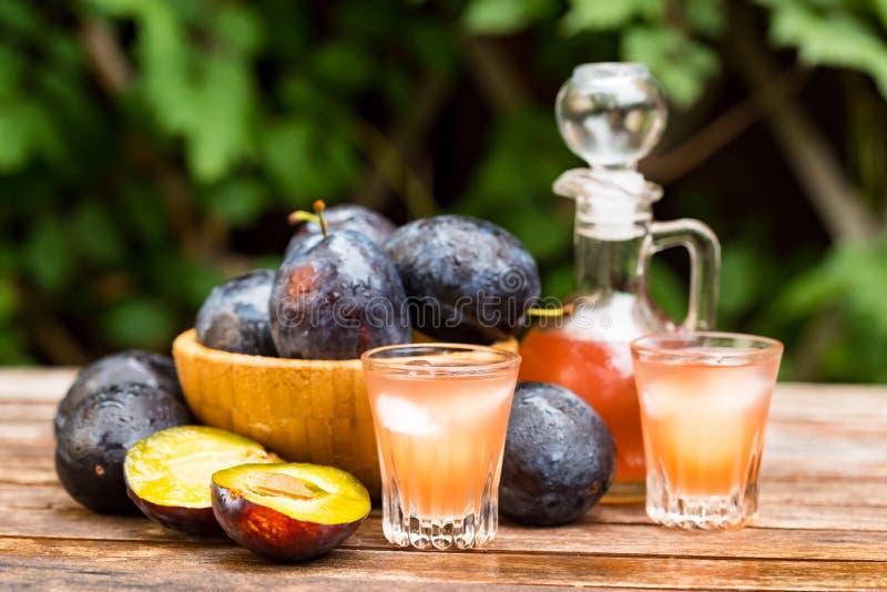 Brandy o slivovitz della prugna con le prugne mature fresche fotografie stock libere da diritti