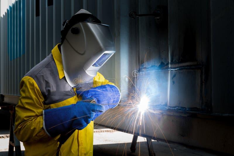 Branscharbetare med svetsningstål som reparerar behållarestrukturen fotografering för bildbyråer