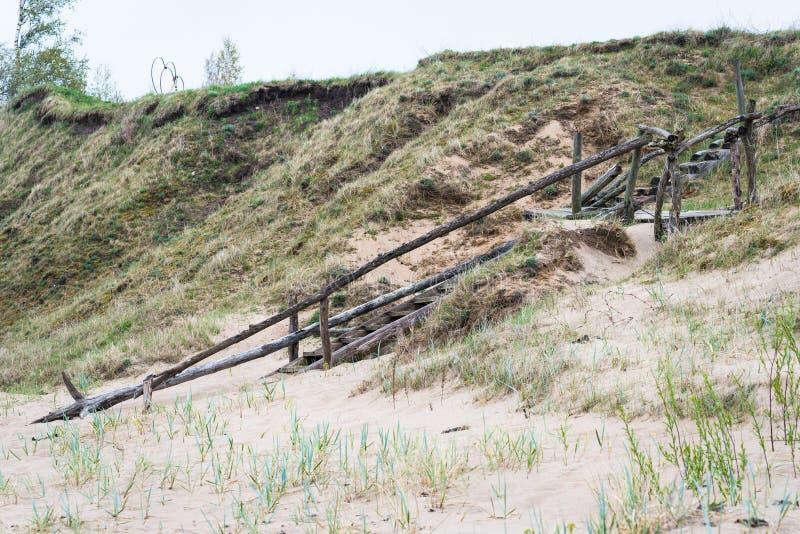 Brant kust och gammal trätrappa som leder upp royaltyfri bild