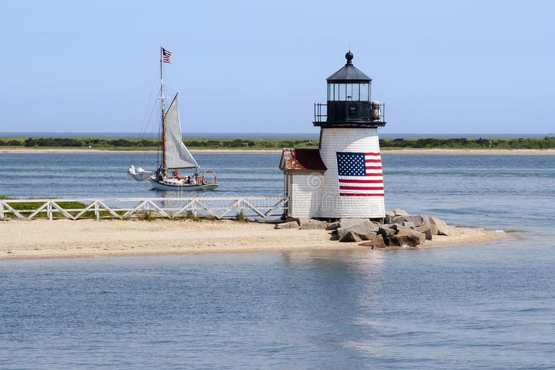 Patriotic Lighthouse Guides a Sailboat out of Nantucket Island H royalty free stock photo