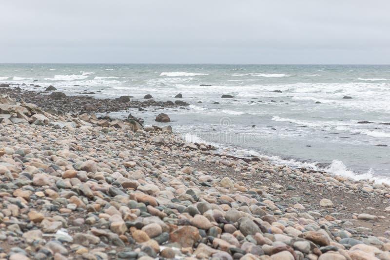 Brant stenig strand på molnig vinterdag royaltyfri bild