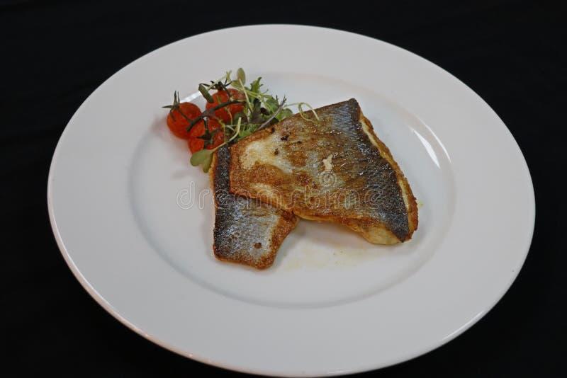 Branzino fritto in un piatto bianco immagini stock libere da diritti