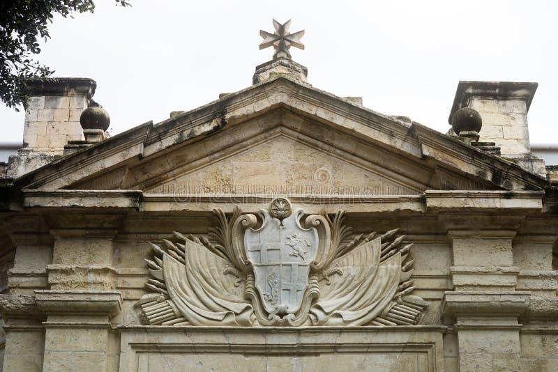 Brasão e cruz maltesa cinzeladas pedra acima da entrada fotos de stock royalty free