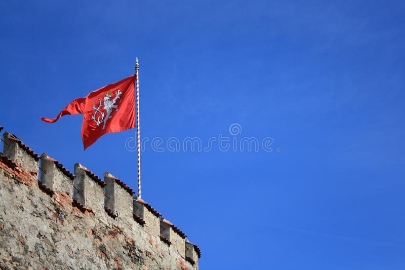 A brasão vermelha de República Checa A bandeira com o leão na fortaleza no céu azul fotos de stock