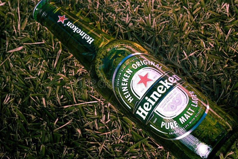 Brasília, ομοσπονδιακή περιοχή - Βραζιλία 18 Ιουνίου 2019 Φωτογράφισε ένα μπουκάλι της μπύρας της Heineken στο χορτοτάπητα με την στοκ φωτογραφία με δικαίωμα ελεύθερης χρήσης