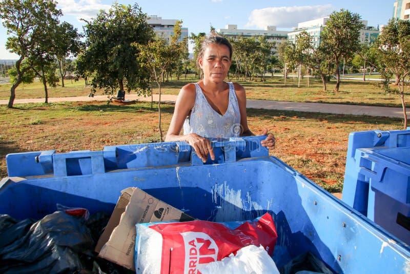 Brasília, D f , Brasil 11 de junho de 2019: Uma senhora pobre que escava através do lixo em uma vizinhança afluente para tentar e fotos de stock