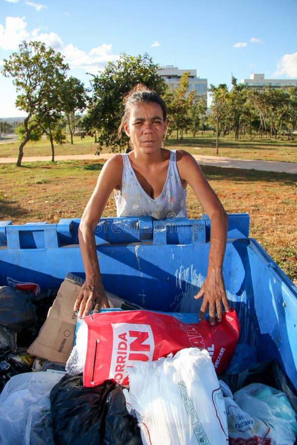 Brasília, D f , Brasil 11 de junho de 2019: Uma senhora pobre que escava através do lixo em uma vizinhança afluente para tentar e foto de stock