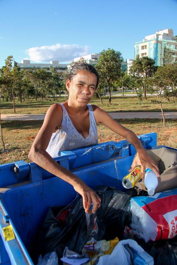 Brasília, D f , Brasil 11 de junho de 2019: Uma senhora pobre que escava através do lixo em uma vizinhança afluente para tentar e foto de stock royalty free