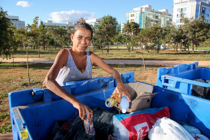 Brasília, D f , Brasil 11 de junho de 2019: Uma senhora pobre que escava através do lixo em uma vizinhança afluente para tentar e fotografia de stock