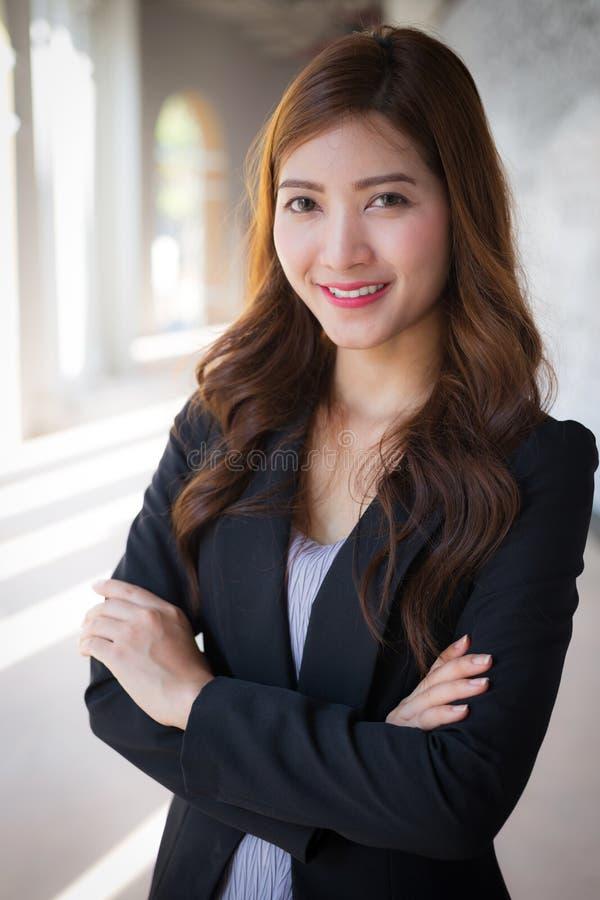 Bras croisés par position de femme d'affaires avec le visage de sourire images stock