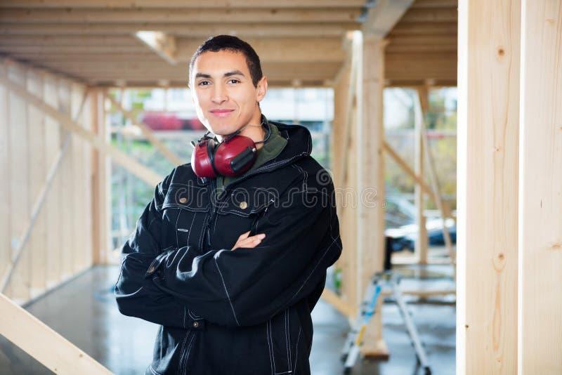 Bras de Smiling While Standing de charpentier croisés au site photo stock