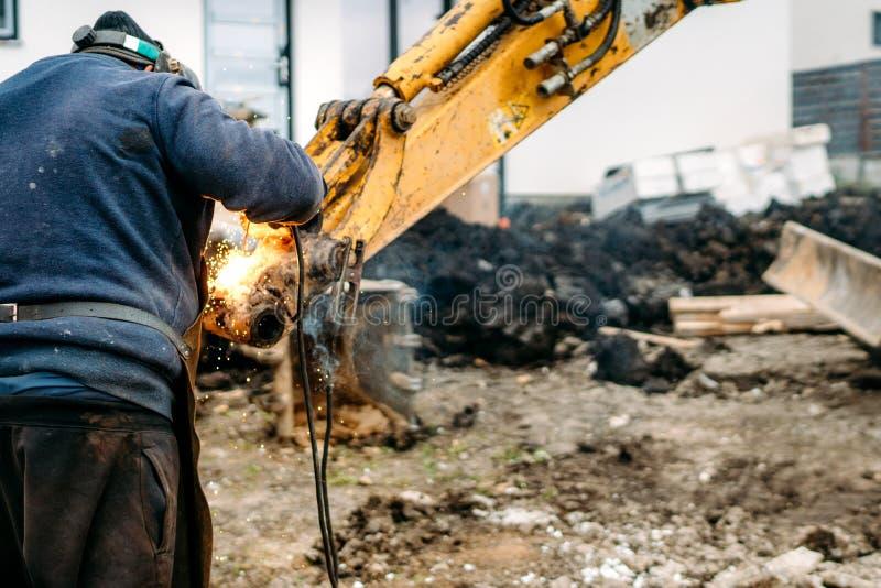 Bras de soudure d'excavatrice de travailleur sur le chantier de construction photographie stock libre de droits