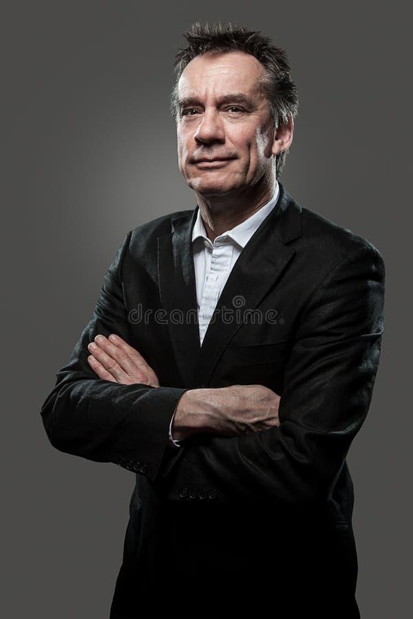 Bras de sourire d'homme d'affaires pliés sur le gris photos stock