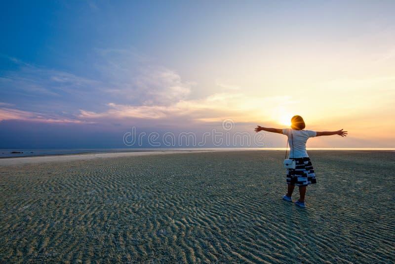 Bras debout de femme tendus au coucher du soleil image libre de droits