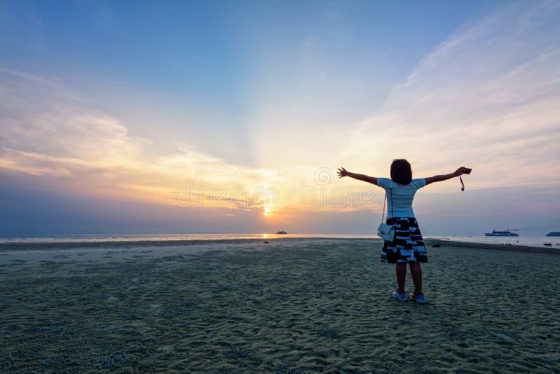 Bras debout de femme tendus au coucher du soleil photo libre de droits