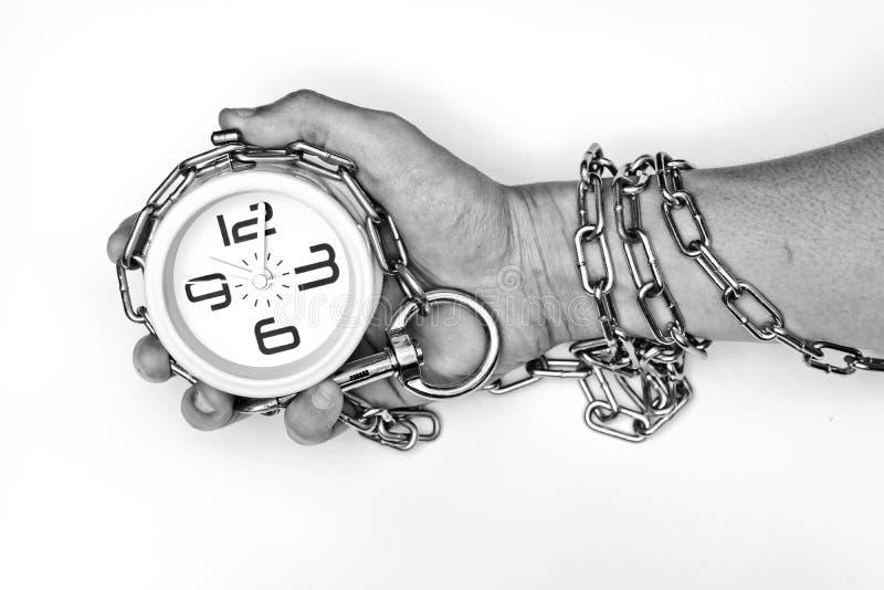 Bras enchaîné avec une horloge photographie stock