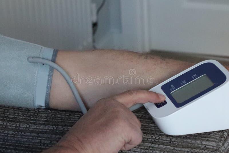 Bras et machine adultes de tension artérielle dans la maison lecture record pour des médecins photographie stock libre de droits