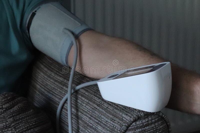 Bras et machine adultes de tension artérielle dans la maison lecture record pour des médecins photo stock