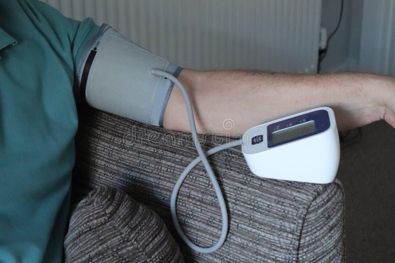 Bras et machine adultes de tension artérielle dans la maison lecture record pour des médecins image stock