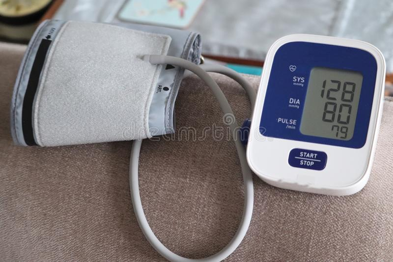 Bras et machine adultes de tension artérielle dans la maison lecture record pour des médecins images libres de droits