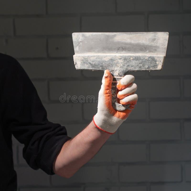 Bras gauche masculin dans le gant tenant le grand couteau de mastic texturisé sale noir sur une texture linéaire abstraite large  images stock