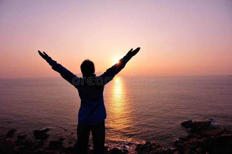 Bras ouverts de femme reconnaissante au lever de soleil photographie stock libre de droits