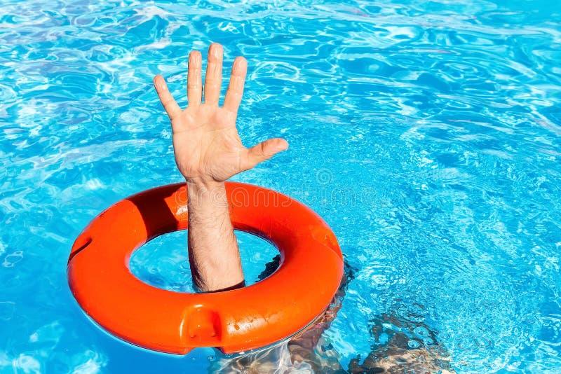 Bras par la balise orange dans la piscine photographie stock libre de droits