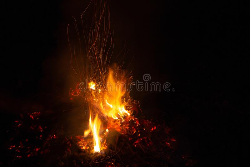 Brasan i natten, den h?rliga apelsinen mousserar p? en svart bakgrund royaltyfria bilder