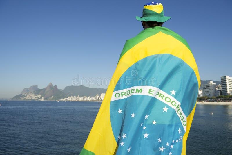 Brasileiro envolvido na bandeira no mar foto de stock royalty free