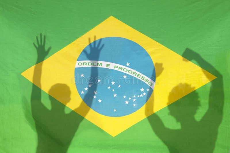 Brasilianer som firar skuggor på den Brasilien flaggan arkivbild
