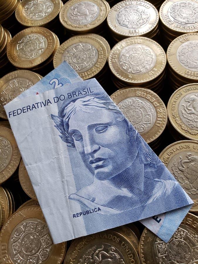 brasilianische Banknote von zwei Reais und mexikanische Münzen von zehn Pesos lizenzfreie stockfotografie