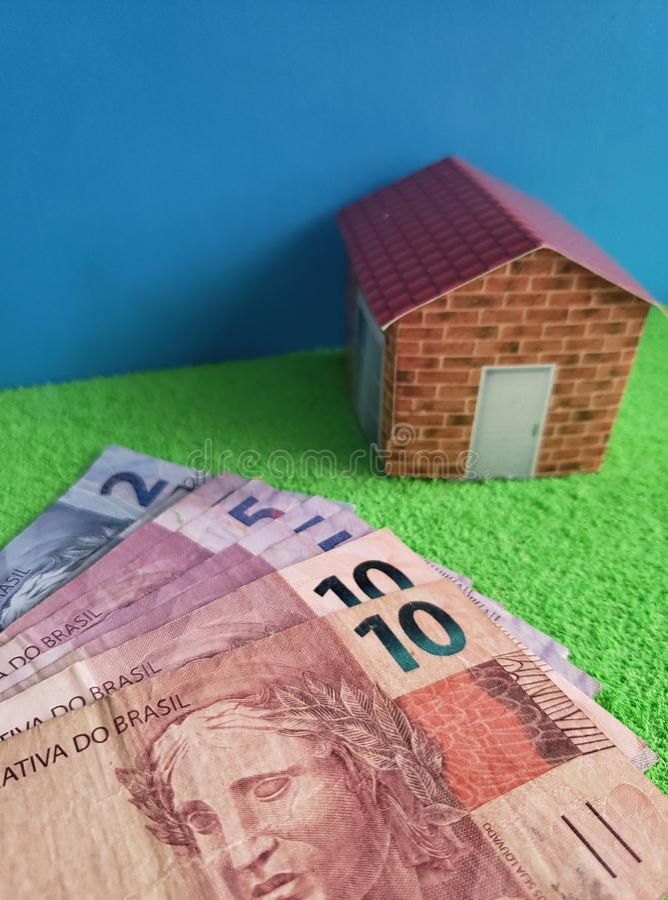 brasilianische Banknoten und Zahl eines Hauses auf grüner Oberfläche und blauem Hintergrund lizenzfreies stockbild