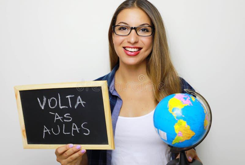 Brasilianische junge Holdingkugel und -tafel des weiblichen Lehrers mit Portugiesisch geschrieben lizenzfreie stockbilder